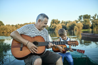Grandfather teaching grandson playing guitar - ZEDF01497