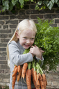 A young girl holding a large bunch of carrots. - MINF00275