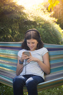 Smiling girl with headphones sitting in hammock looking at smartphone - LVF07320