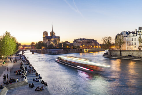 France, Paris, Tourist boat on Seine river with Notre Dame cathedral in background - WDF04716