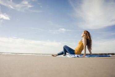 Netherlands, Zeeland, redheaded woman relaxing on the beach - KNSF04193