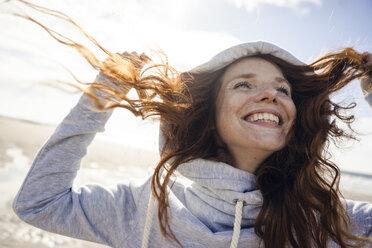 Netherlands, Zeeland, portrait of happy redheaded woman wearing hooded jacket on the beach - KNSF04196