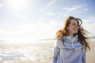 Netherlands, Zeeland, portrait of redheaded woman with blowing hair on the beach - KNSF04199