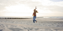 Netherlands, Zeeland, happy woman dancing on the beach - KNSF04205