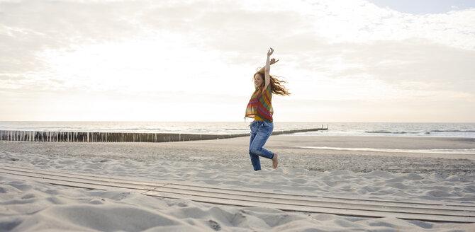 Netherlands, Zeeland, happy woman dancing on the beach - KNSF04205