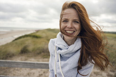 Netherlands, Zeeland, portrait of happy redheaded woman on the beach - KNSF04208