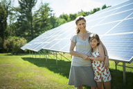 A child and her mother in the fresh open air, beside solar panels on a sunny day at a farm in New York State, USA. - MINF00464