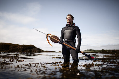 A man in a wetsuit, standing on the shore with a large spear fishing harpoon. - MINF00476