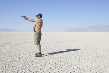 A man aiming a hand gun, holding it with his arm outstretched, standing in a vast, barren desert. - MINF00503