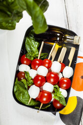 Lunch box of skewered cherry tomatoes and mozzarella cheese balls with basil leaves and vinaigrette - SBDF03670