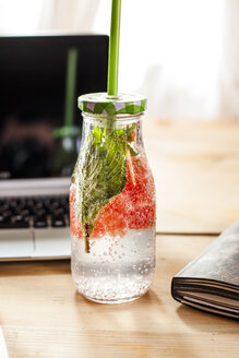 Glass bottle of detox water infused with red grapefruit and mint on desk - SBDF03673