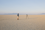 Man with camera and tripod on the flat saltpan or playa of Black Rock desert, Nevada. - MINF00723