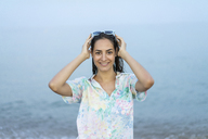 Portrait of smiling woman in front of the sea - AFVF00870
