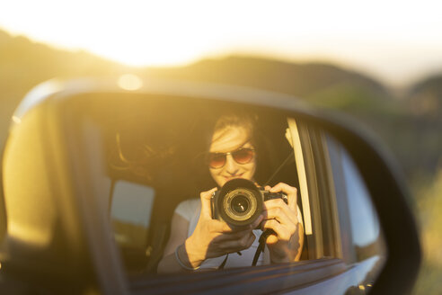 Young woman taking picture of her mirror image in her car - AFVF00889