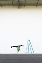 Acrobat training one-armed handstand next to ladder - AFVF00894
