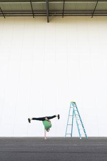 Acrobat training one-armed handstand next to ladder - AFVF00894