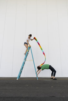 Two acrobats exercising trick on a ladder with a ribbon - AFVF00900