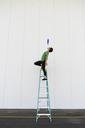 Acrobat standing on ladder, juggling - AFVF00912