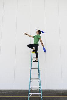 Acrobat standing on ladder, juggling - AFVF00915