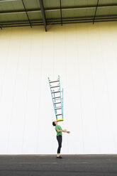 Acrobat balancing ladder on his face - AFVF00930
