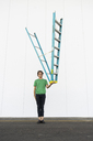 Acrobat balancing ladder upside down in his hand - AFVF00936