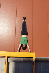 Acrobat performing handstand on yellow frame - AFVF00948