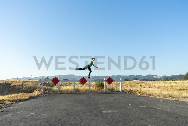 Acrobat balancing on barrier - AFVF00957