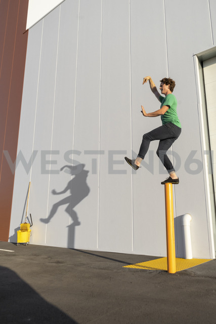 Acrobat standing on pole, casting shadow at cleaning bucket - AFVF00975