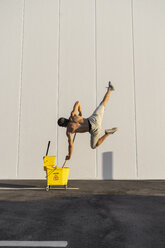 Acrobat playing with cleaning bucket and mop - AFVF00990