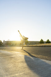 Acrobat practicing one-armed handstand on a road at sunset - AFVF00993