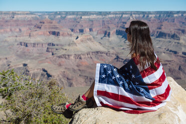 USA, Arizona, woman wrapped in American flag enjoying view of Grand Canyon National Park - GEMF02171