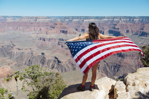 USA, Arizona, back view of woman with American flag enjoying view of Grand Canyon National Park - GEMF02174