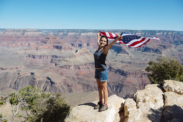 USA, Arizona, smiling woman with American flag at Grand Canyon National Park - GEMF02177