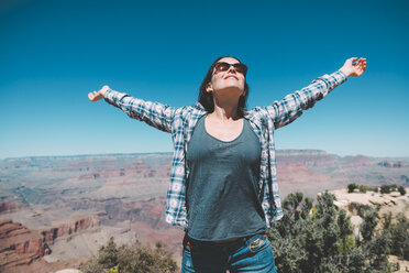 USA, Arizona, Grand Canyon National Park, happy woman  in front of Grand Canyon - GEMF02189