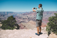 USA, Arizona, Grand Canyon National Park, Grand Canyon, man taking photos with smartphone - GEMF02192