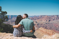 USA, Arizona, Grand Canyon National Park, back view of kissing couple sitting side by side - GEMF02198