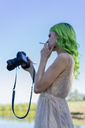 Young woman with dyed green hair smoking cigarette in nature while looking at display of digital camera - AFVF00994