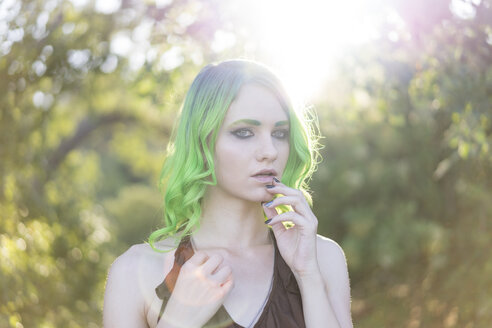 Portrait of young woman with dyed green hair and eyebrows at backlight - AFVF01000