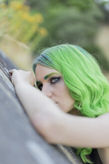 Portrait of young woman with dyed green hair and eyebrows in nature - AFVF01006