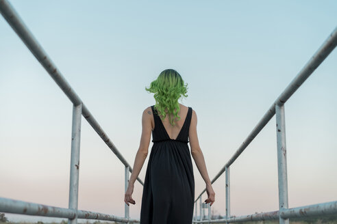 Back view of young woman with dyed green hair on a footbridge - AFVF01012