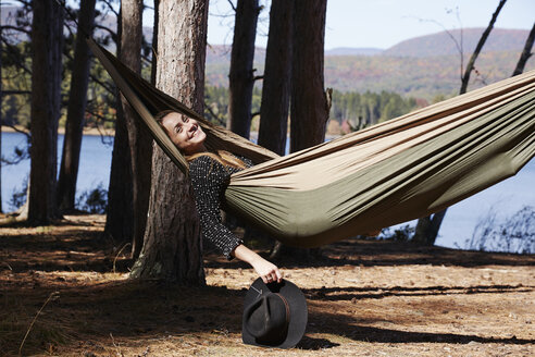 A woman lying in a hammock relaxing, under the pine trees by a lake. - MINF01041