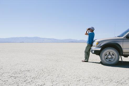 Man standing on vast desert, looking through binoculars and leaning against truck, Black Rock Desert - MINF01050