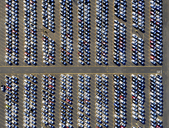 Aerial view of a car distribution centre, new cars parked in rows on a lot ready for sale. - MINF01119