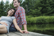 A couple relaxing on a jetty overlooking a mountain lake. - MINF01239