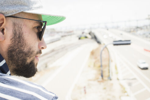 Close up of a bearded young man wearing sunglasses and a baseball cap. - MINF01368