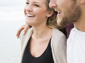 Close up of a smiling young man and young woman on a beach. - MINF01386