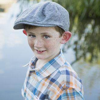 A young boy wearing a checked shirt and cloth cap with a large brim standing on a riverbank. - MINF01527