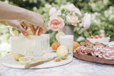 Close up of a woman preparing drinks, a wooden board with cold cuts on a table in a garden. - MINF01641
