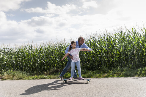 Mature man helping little girl to learn skateboarding - UUF14557