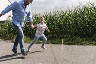 Mature man and little girl running on street, laughing - UUF14560
